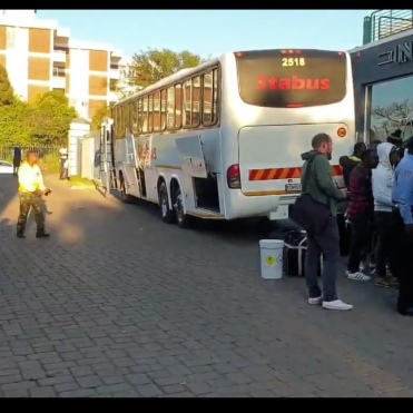 Nigerians boarding a bus to the airport