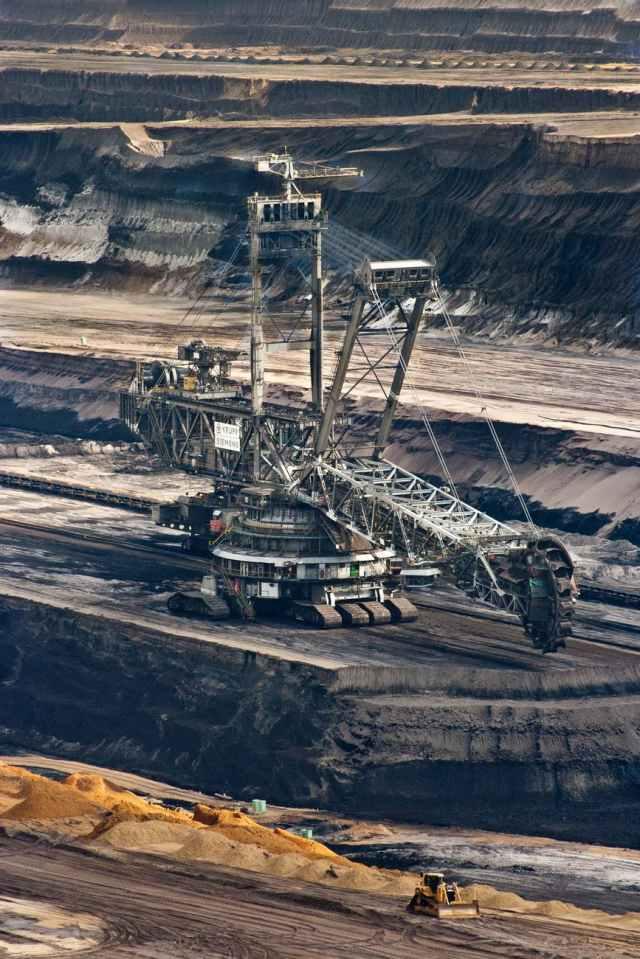 silver steel mining crane on black rocky soil during daytime