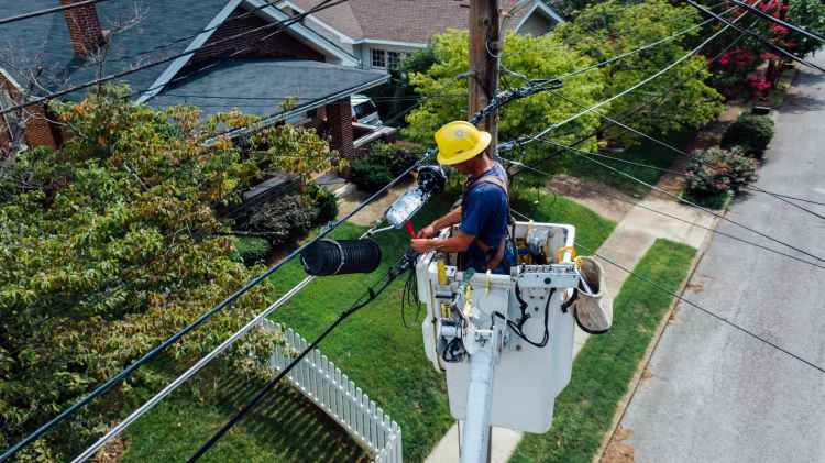 photography of man repairing electrical wires