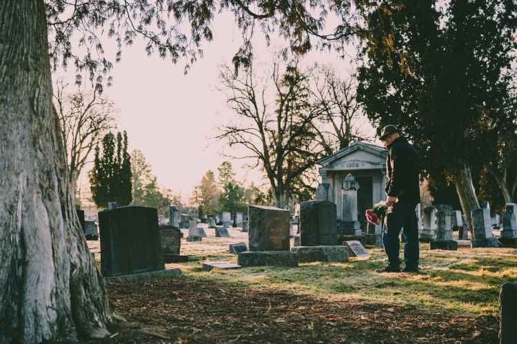 man in black jacket standing in front of grave