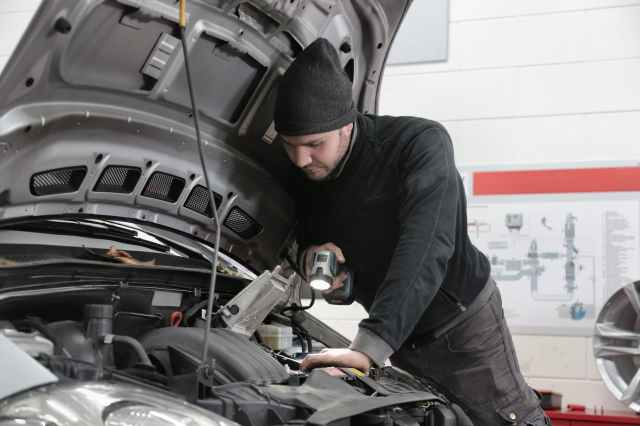 man in black jacket and black knit cap inspecting car engine