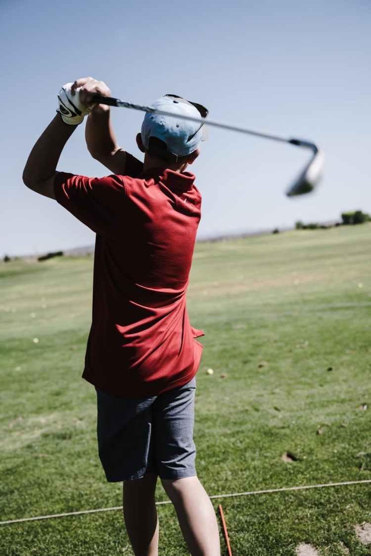 man swinging golf club facing grass field